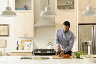 Mixed race man cooking in kitchen - BLEF13045