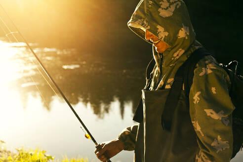 Mari man holding fishing rod at lake - BLEF13054