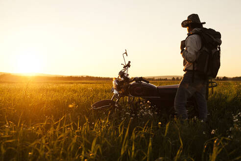 Mari man standing in field with motorcycle - BLEF13060
