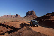 Car driving on remote road through rock formations, Monument Valley Tribal Park, Utah, United States - BLEF13081