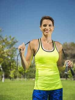 Mixed race woman holding jump rope in park - BLEF13120