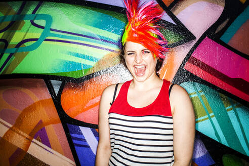 Caucasian woman in colorful wig laughing near graffiti wall - BLEF13130