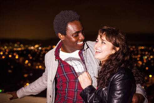 Couple hugging near scenic view of cityscape at night - BLEF13136