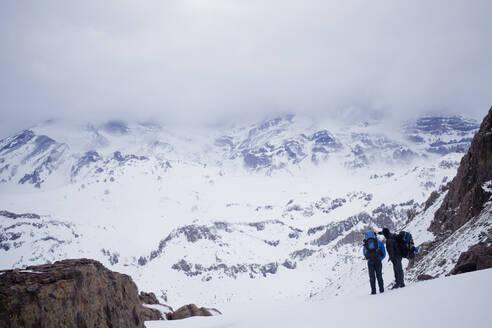 Hispanic hikers admiring snowy scenic mountains - BLEF13376