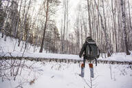 Mixed race man walking in snowy forest - BLEF13391
