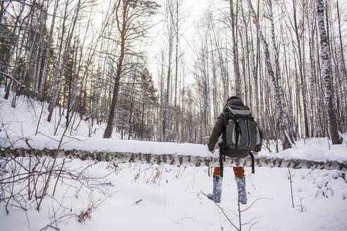 Mixed race man walking in snowy forest - BLEF13391