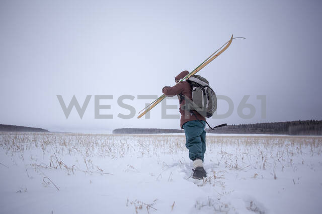 Mixed race man carrying skis in snowy field - BLEF13397 - Aliyev Alexei Sergeevich/Westend61