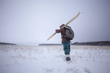 Mixed race man carrying skis in snowy field - BLEF13397