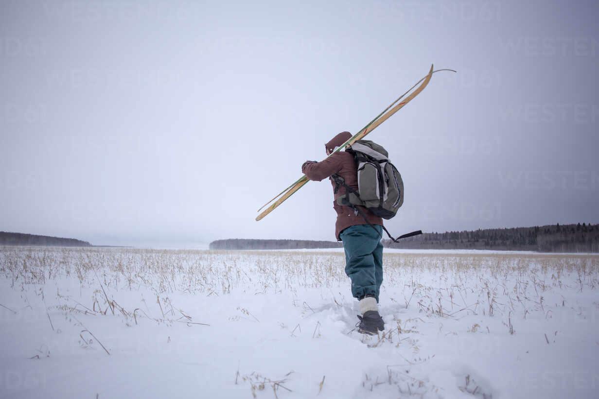 Mixed race man carrying skis in snowy field - BLEF13397 - Aliyev Alexei Sergeevich/Westend61