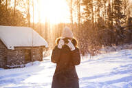 Caucasian woman photographing in snow - BLEF13403