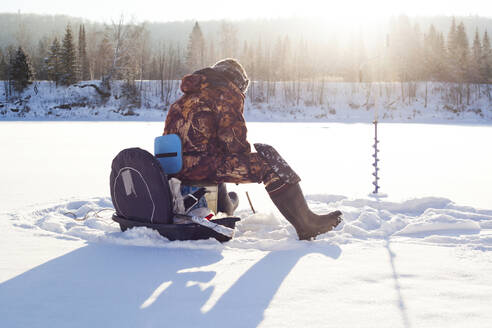 Mari man ice fishing in snowy field - BLEF13409