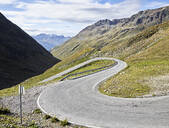 Winding road on mountain against cloudy sky during sunny day, Tyrol State, Austria - CVF01428