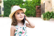 Portrait of toddler girl with straw hat on the phone - GEMF03031