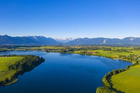Scenic view of Riegsee lake and green landscape against clear blue sky, Germany - LHF00659