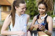 Two smiling sporty young women checking cell phone - JSRF00485