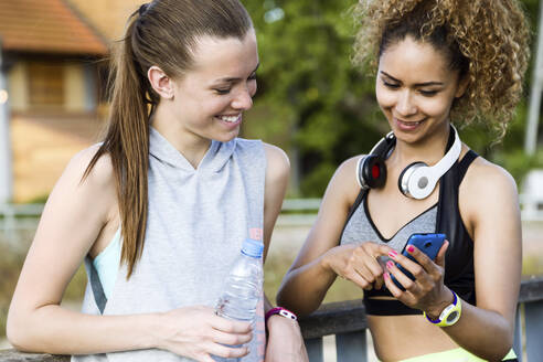 Portrait of two fit and sporty young women using mobile phone in the park. - JSRF00485