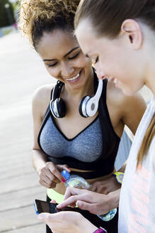 Portrait of two fit and sporty young women using mobile phone in the park. - JSRF00494