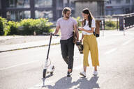Young couple with electric scooter and smartphone walking on the street - UUF18385