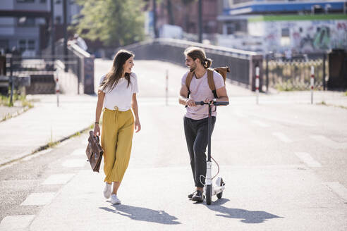 Young couple with electric scooter walking and talking on the street - UUF18397