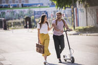 Happy young couple with electric scooter walking on the street - UUF18400