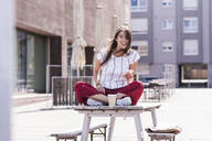 Happy young woman sitting on table in a beer garden with cell phone - UUF18463