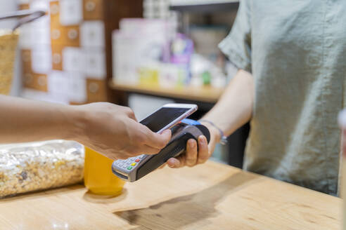 Customer paying cashless with smartphone in a shop - AFVF03610