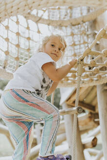 Girl climbing in jungle gym on a playground - DWF00456