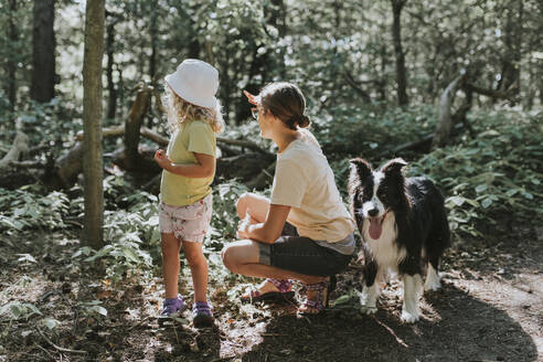 Mother with daughter and dog in a forest - DWF00459