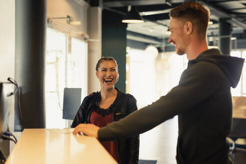 Laughing young woman talking to coach at front desk of a gym - SEBF00121