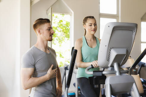Personal trainer talking to young woman exercising on step machine in fitness gym - SEBF00130