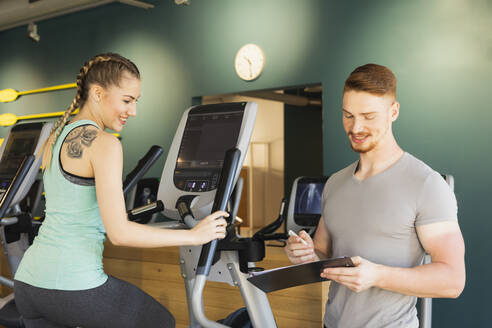 Young woman exercising on step machine in fitness gym with personal trainer taking notes - SEBF00133