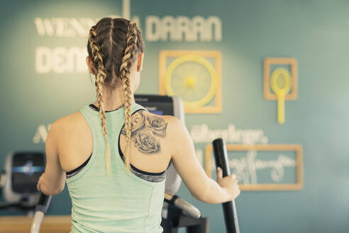 Rear view of young woman exercising on step machine in fitness gym - SEBF00136