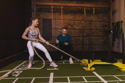 Young woman exercising in fitness gym with personal trainer pulling rope - SEBF00142