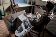 Female artist sitting in her studio with paintings - OGF00101