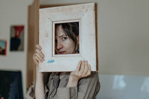 Portrait of a female painter in her studio looking through picture frame - OGF00110