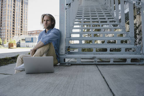 Young man sitting at stairs with laptop - KNSF06171