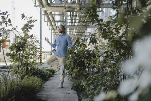 Young man meditating on pavement surrounded by plants - KNSF06174