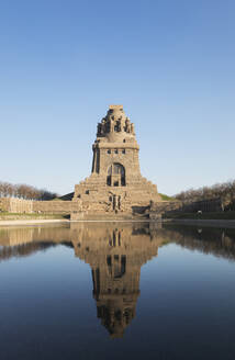 Lake of tears with reflection of Völkerschlachtdenkmal against clear blue sky, Saxony, Germany - GWF06202