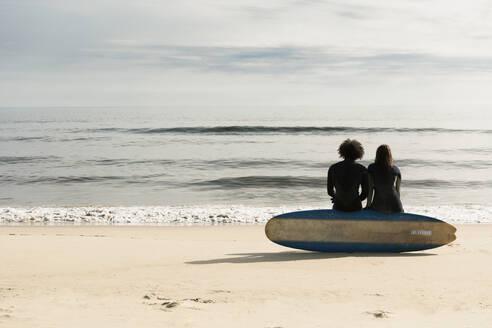 Surfers sitting on board on beach - BLEF13619