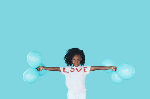 Little afro girl In front of a blue wall and holding balloons - JCMF00082