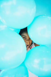 Little afro girl In front of a blue wall and holding balloons - JCMF00088