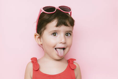 Portrait of little girl sticking out tongue in front of pink background - GEMF03037