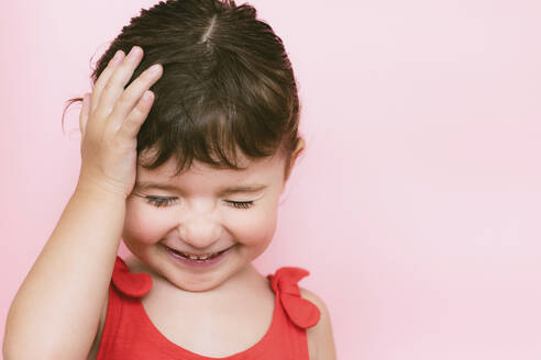 Portrait of giggling little girl in front of pink background - GEMF03040