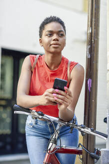 Portrait of young woman leaning on handle bar of bicycle looking at distance - JSMF01207