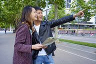 Tourist couple visiting the city and holding a map, Barcelona, Spain - GEMF03044