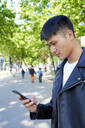Young man using cell phone, Barcelona, Spain - GEMF03053