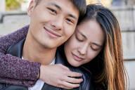 Happy young woman hugging boyfriend outdoors - GEMF03098