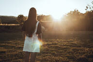 Rear view of young woman standing in field landscape at sunset - ACPF00574