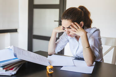 Frustrated female student with documents at desk at home - LJF00589
