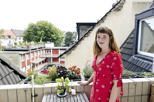 Deutschland,NRW,Ruhrgebiet,Stadt Essen,Junge Frau im roten Kleid auf dem Balkon - FLLF00254